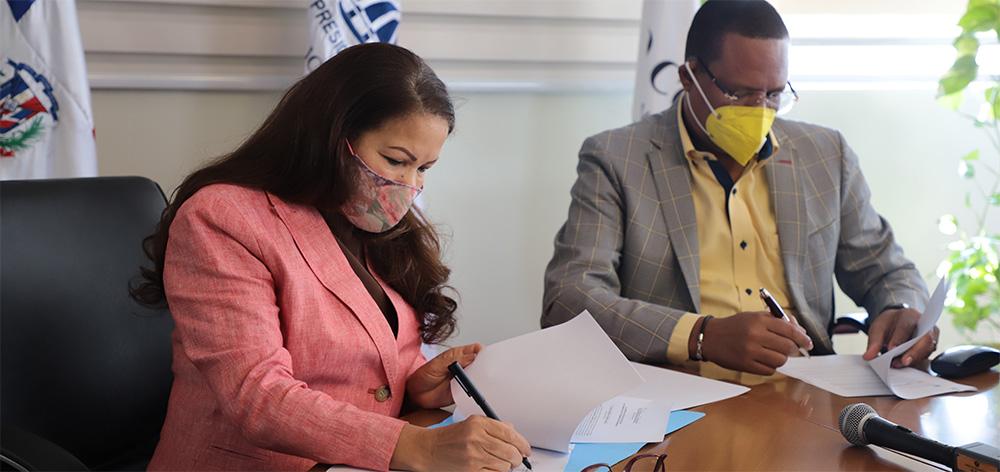 La directora de la ADESS, Digna Reynoso y el titular de Pro Consumidor, Eddy Alcántara, en el momento que firman el acuerdo.