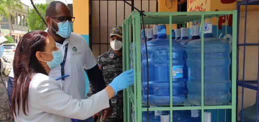 La subdirectora administrativa de Pro Consumidor, María Teresa Paulino, supervisa botellones de agua plásticos en un establecimiento comercial.