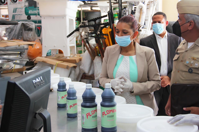 """La subdirectora Administrativa de Pro Consumidor, María Teresa Paulino, junto a inspectores y oficiales de la institución decomisan productos químicos utilizados para la fabricación de """"ácido del diablo""""."""